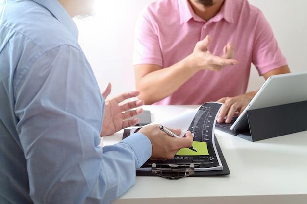 Uomini d'affari che lavorano insieme su un documento e che utilizzano smartphone