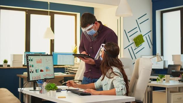 Uomini d'affari che discutono di strategia finanziaria guardando il computer che indossa una maschera di protezione nella nuova normale stanza dell'ufficio. team multietnico che analizza grafici, lavorando insieme rispettando la distanza sociale.