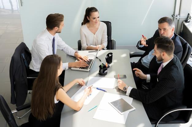 Uomini d'affari che discutono insieme nella sala conferenze durante la riunione in ufficio.