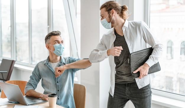 Uomini d'affari riuniti in ufficio che indossano maschere