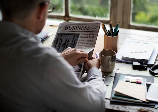 Businesspeople reading newspaper at office aggiornamento notizie