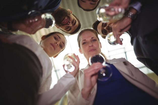 Persone di affari che tostano bicchieri di champagne
