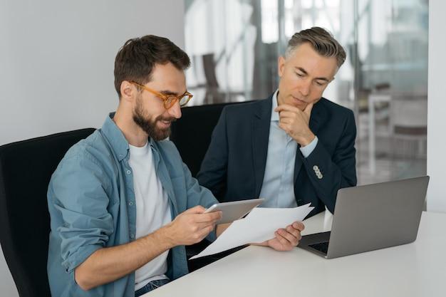 Persone di affari che utilizzano tavoletta digitale, computer portatile, parlando, pianificando l'avvio, lavorando in ufficio