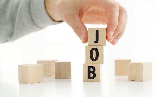 Imprenditore dando blocco di legno con testo di lavoro al candidato