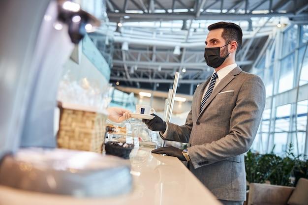 Uomo d'affari che acquista una tazza di caffè al bancone