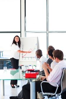 Businessswoman che riferisce alle cifre di vendite in una riunione