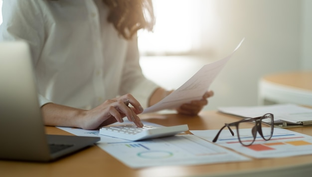 Donna d'affari o ragioniere che lavora responsabile finanziario ricerca contabilità del processo calcolare con la calcolatrice per analizzare la revisione delle informazioni sulle azioni dei dati del grafico di mercato sul tavolo in ufficio.