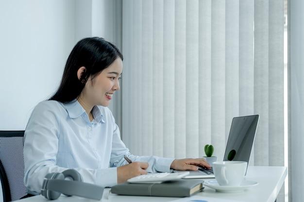 Imprenditrice analisi del grafico e riunione videoconferenza con il laptop in ufficio a casa per la definizione di obiettivi aziendali sfidanti e la pianificazione per raggiungere il nuovo obiettivo.