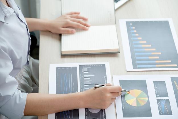 Imprenditrice analizza il grafico con il laptop in ufficio per stabilire obiettivi aziendali impegnativi.