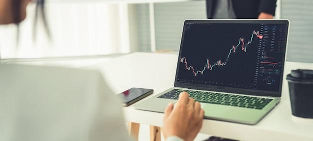 Imprenditrice nell'analizzare i dati del mercato azionario utilizzando il computer portatile in modo competente