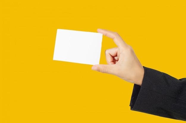 Tenuta asiatica della donna di affari e indicato un biglietto da visita su fondo giallo
