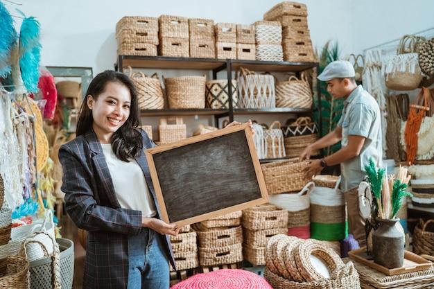 La donna di affari in una giacca sportiva che tiene una lavagna sta in un negozio di artigianato con un cliente che sta selezionando l'artigianato