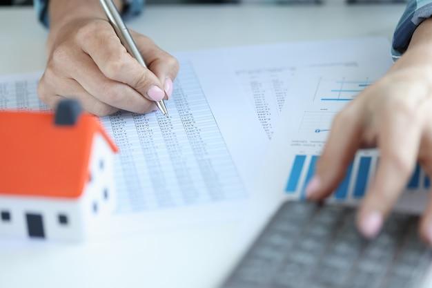 La donna di affari calcola l'interesse sulla calcolatrice sui pagamenti per l'acquisto della casa