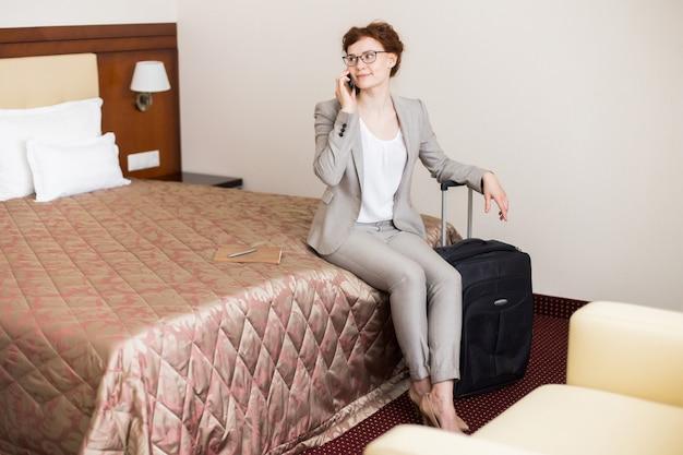 Donna di affari che chiama dalla camera di albergo