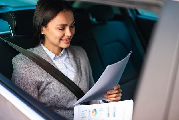 Donna di affari nell'auto che esamina i documenti
