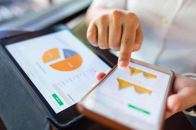 Donna di affari controlla i dati in smartphone e tablet