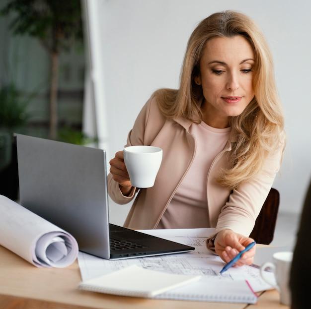Imprenditrice controllando le note del suo collega