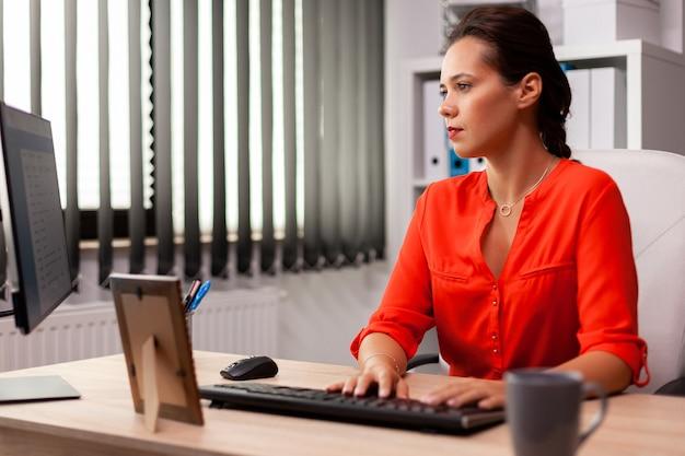Businesswoman manager aziendaleworking e digitando il rapporto finanziario. datore di lavoro concentrato di successo con una carriera impegnata seduto alla scrivania in ufficio utilizzando un pc moderno.