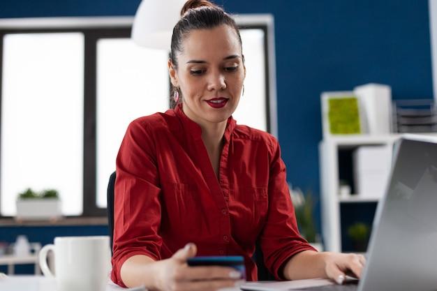 Donna d'affari nel posto di lavoro dell'ufficio aziendale in possesso di carta di credito che fa lettura online del gestore dei pagamenti...