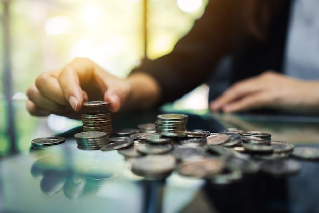 Donna di affari che conta e che impila le monete sulla tavola per soldi di risparmio e concetto finanziario