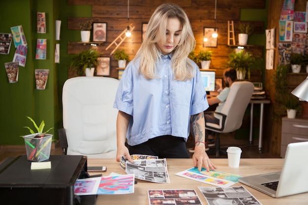 Imprenditrice in ufficio creativo guardando i disegni. stilista donna.