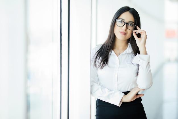 Imprenditrice attraversato le mani ritratto in ufficio con finestre panoramiche. concetto di affari