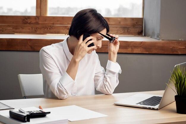 La donna d'affari alla scrivania documenta lo stile di vita professionale dello studio di lavoro