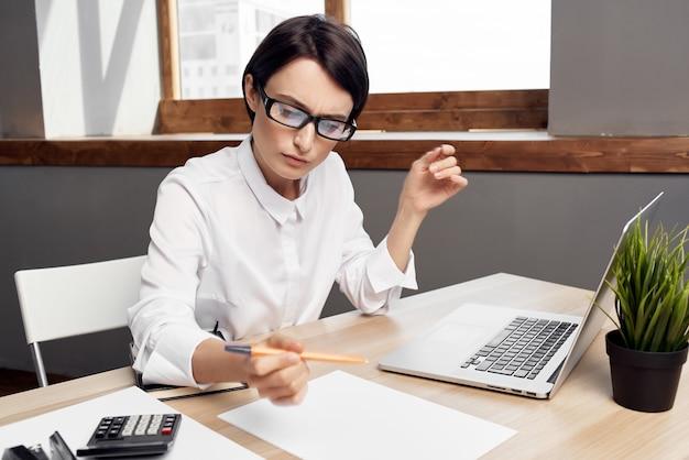 Donna d'affari alla scrivania segretaria esecutiva sfondo chiaro