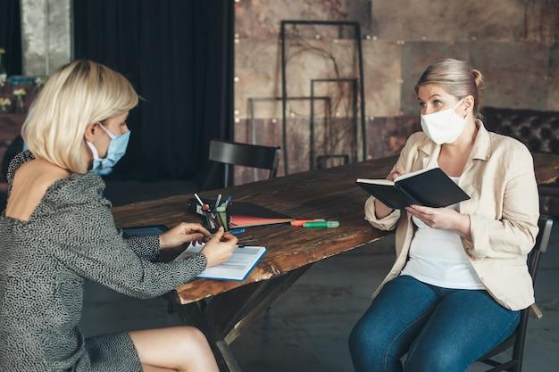 Imprenditrice discutendo durante la quarantena sugli affari e indossare maschera medica sul viso