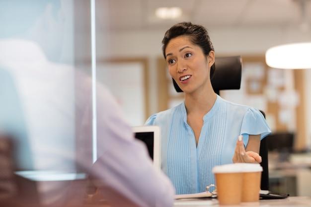 Imprenditrice discutendo con un collega in ufficio