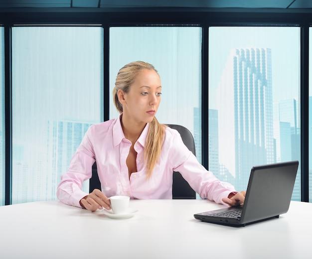 Donna di affari che beve un caffè nel suo ufficio