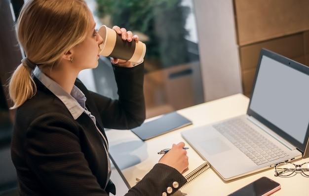 Donna di affari che beve caffè e che utilizza computer tablet in una caffetteria