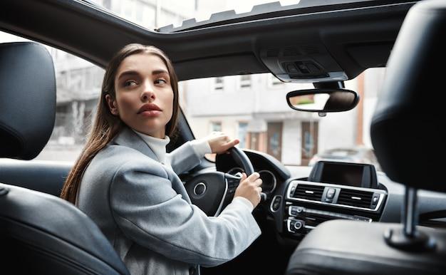 Driver di donna d'affari guardando dietro, eseguire il backup di auto sul parcheggio. donna che guida in retromarcia.