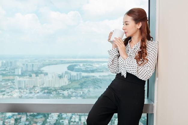 Donna di affari che gode della tazza di caffè in ufficio