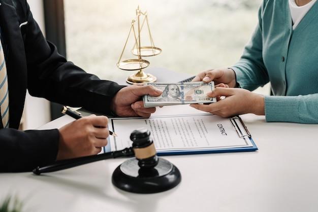 La donna d'affari ha dato i soldi all'avvocato per aiutare con il caso e firmare il contratto in ufficio.