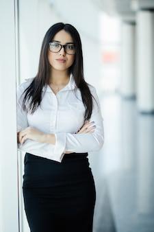 Imprenditrice in bicchieri incrociate le mani ritratto in ufficio con finestre panoramiche. concetto di affari