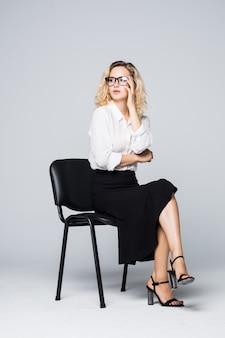 Donna di affari in vetri che si siedono su una sedia isolata sulla parete bianca