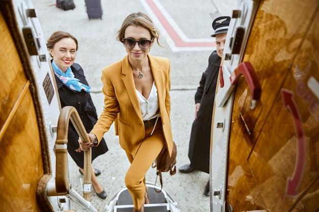 Imprenditrice salendo con i bagagli sulla scala del jet aereo privato. aereo passeggeri moderno. hostess e pilota stanno vicino alla donna. vista dall'alto. aviazione civile. concetto di viaggio aereo e affari