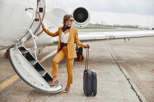 Imprenditrice salendo con i bagagli sulla scala del jet aereo privato. aereo passeggeri moderno. la donna europea sicura indossa un abito formale e occhiali. aviazione civile. concetto di viaggio aereo e affari