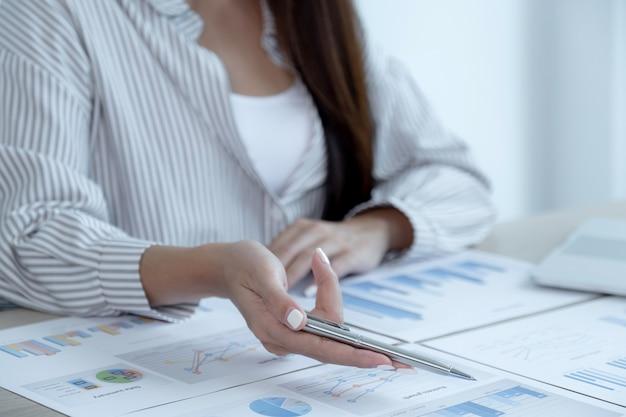 Imprenditrice mano che tiene la penna e l'analisi del grafico con il laptop in ufficio per la definizione di obiettivi aziendali impegnativi e la pianificazione per raggiungere il nuovo obiettivo.