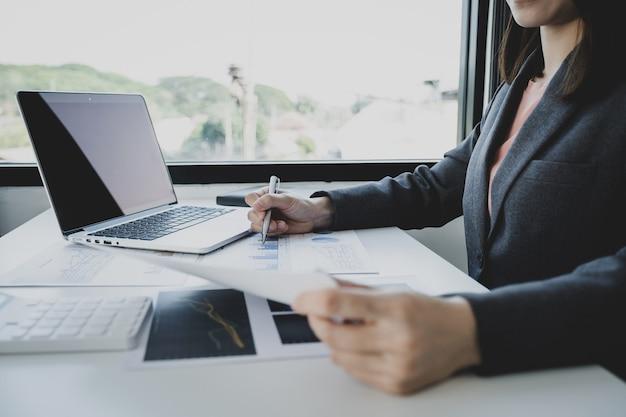 Penna della holding della mano della donna di affari, analisi del grafico con calcolatrice e laptop in ufficio a casa per la definizione di obiettivi aziendali impegnativi