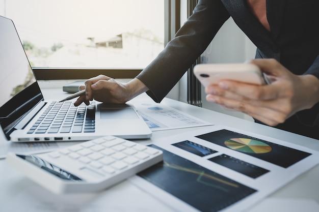 Mano di donna d'affari che tiene smartphone, analisi del grafico con calcolatrice e laptop in ufficio a casa per impostare obiettivi di business impegnativi