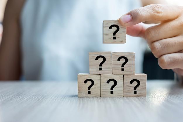 Mano della donna di affari che mette parola del punto interrogativo (?) con il cubo di legno