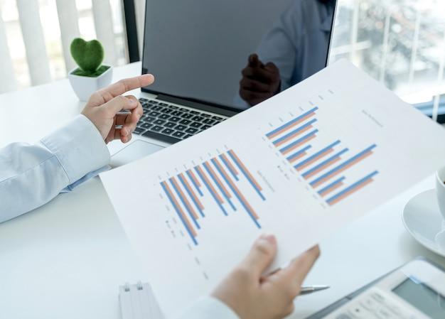 Mano della donna di affari che indica il monitor e l'analisi del grafico e la riunione videoconferenza con il laptop in ufficio a casa per la definizione di obiettivi aziendali impegnativi e la pianificazione di nuovi obiettivi.