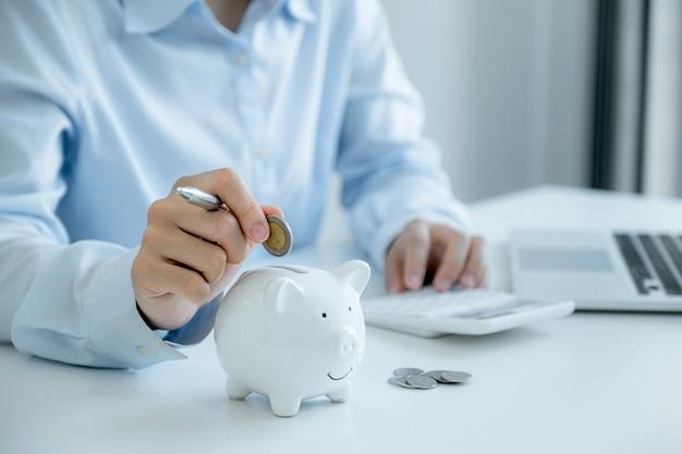 Mano della donna di affari che mette moneta nel salvadanaio, intensificare l'avvio dell'attività verso il successo, risparmiare denaro per il piano futuro e il concetto di fondo pensione.