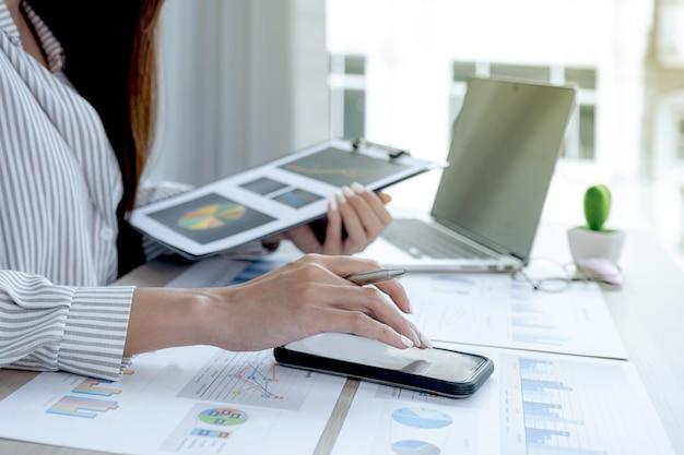 La mano della donna di affari utilizza lo smartphone e analizza il grafico con il laptop in ufficio per impostare obiettivi aziendali sfidanti e pianificare per raggiungere il nuovo obiettivo.