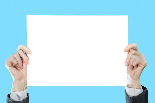 Mani della donna di affari che tengono carta in bianco per copyspace di pubblicità del testo