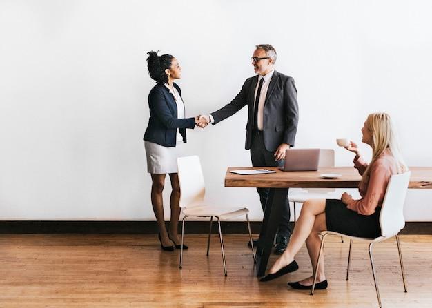 Stretta di mano della donna d'affari con un uomo d'affari
