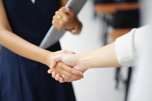 Stretta di mano della donna di affari con il fornitore del socio