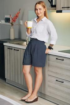 Donna di affari che mangia caffè a casa